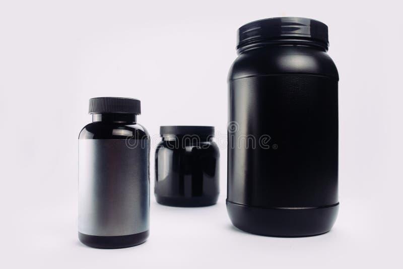 Sportvoeding, Weiproteïne en Gainer Zwarte Plastic Kruiken ISO stock afbeeldingen