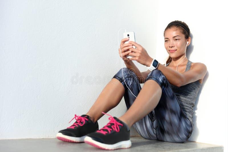 Sportvrouw die aan muziek luisteren die telefoon app en smartwatch geschiktheidsdrijver met behulp van stock foto