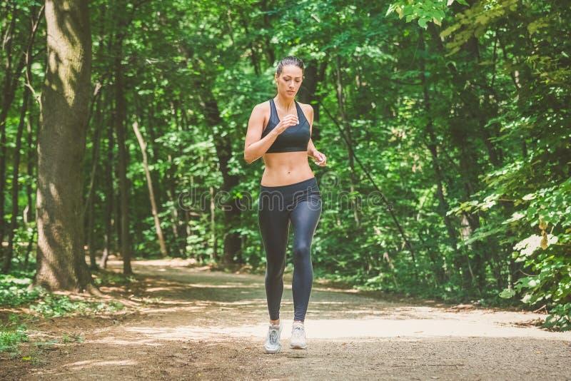 Sportvrouw die in aard lopen stock foto