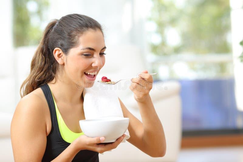 Sportvrouw die graangewassen na sport thuis eten stock fotografie