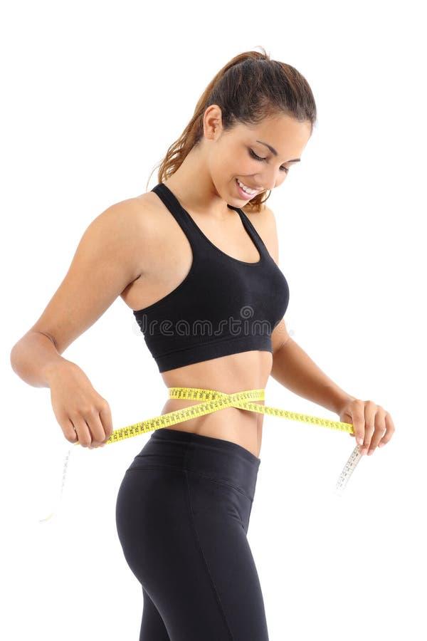 Sportvrouw die haar taille met een maatregelenband meten stock foto's