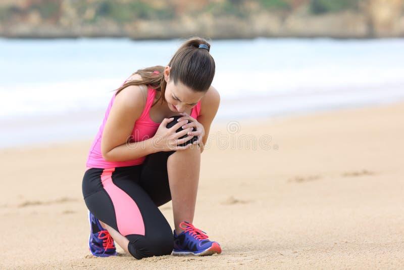 Sportvrouw die knie aan pijn na het lopen lijden royalty-vrije stock fotografie