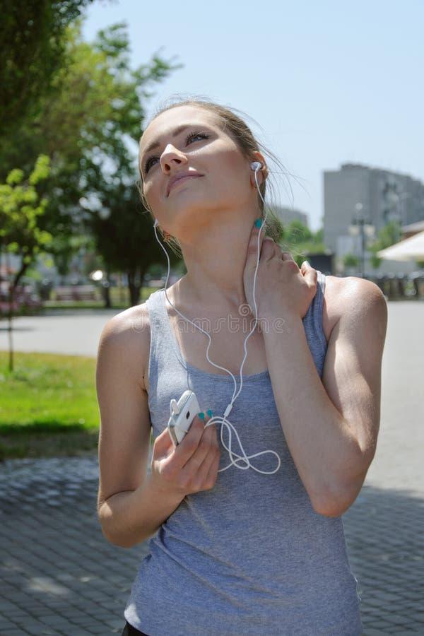 Sportvrouw die omhooggaand en aan muziek luisteren kijken stock afbeeldingen