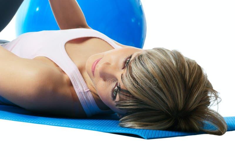 Sportvrouw die op een mat ligt. stock fotografie