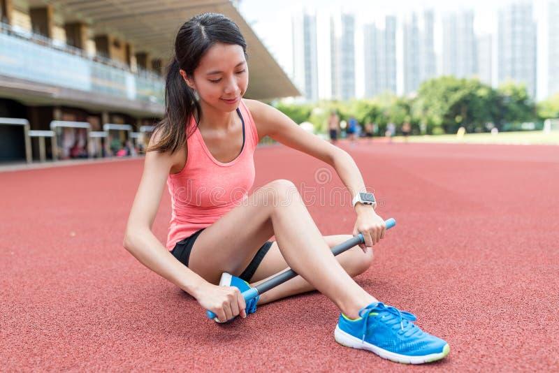 Sportvrouw die rolstok op benen gebruiken stock foto's