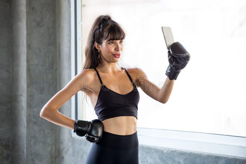 sportvrouw die selfie na oefening in gymnastiek maken het geschiktheidswijfje in sportkleding neemt een onderbreking van training stock fotografie