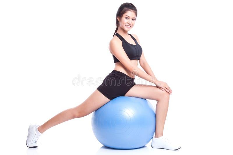 Sportvrouw die uitrekkende fitness oefening op bal doen stock afbeeldingen