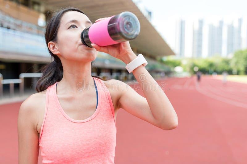 Sportvrouw het drinken van water in het stadion stock foto