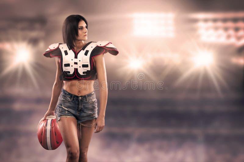 Sportvrouw het stellen met Amerikaans voetbalmateriaal bij het stadion stock foto's