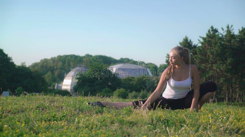 Sportvrouw met blond lang haar die uitrekkende training in openlucht doen royalty-vrije stock afbeelding