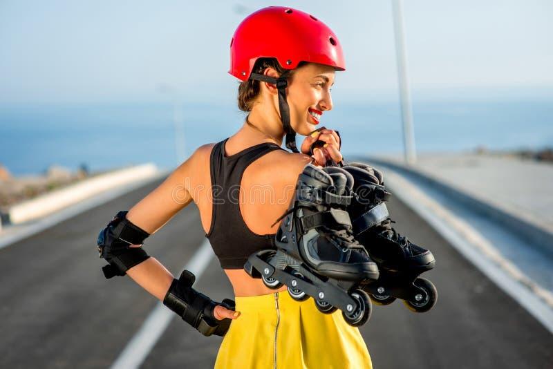 Sportvrouw met rollen op de weg stock afbeelding