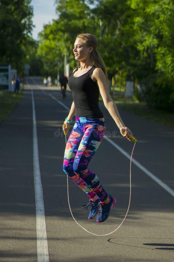 Sportvrouw in park die in openlucht fitness drijvers wearable technologie uitoefenen royalty-vrije stock afbeeldingen