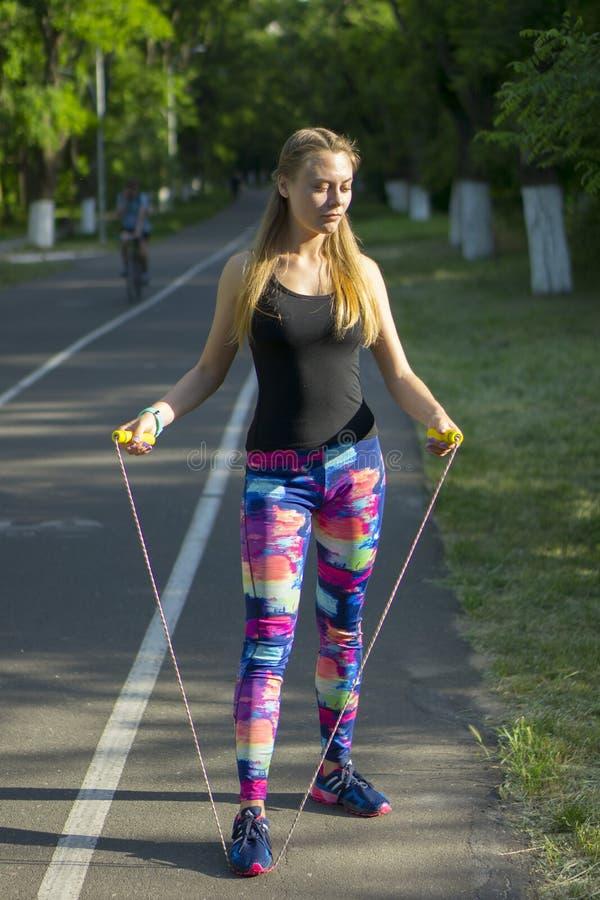 Sportvrouw in park die in openlucht fitness drijvers wearable technologie uitoefenen stock foto's