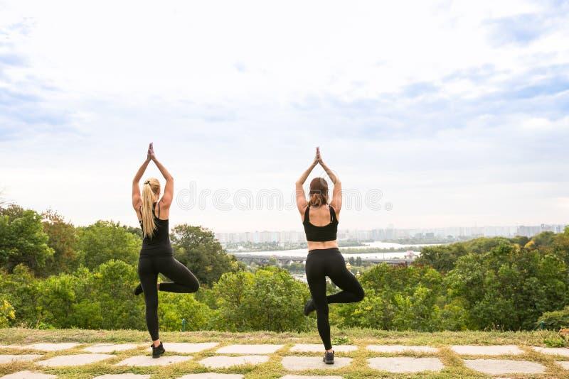 Sportvrouwen die yoga buiten in ochtend doen royalty-vrije stock foto