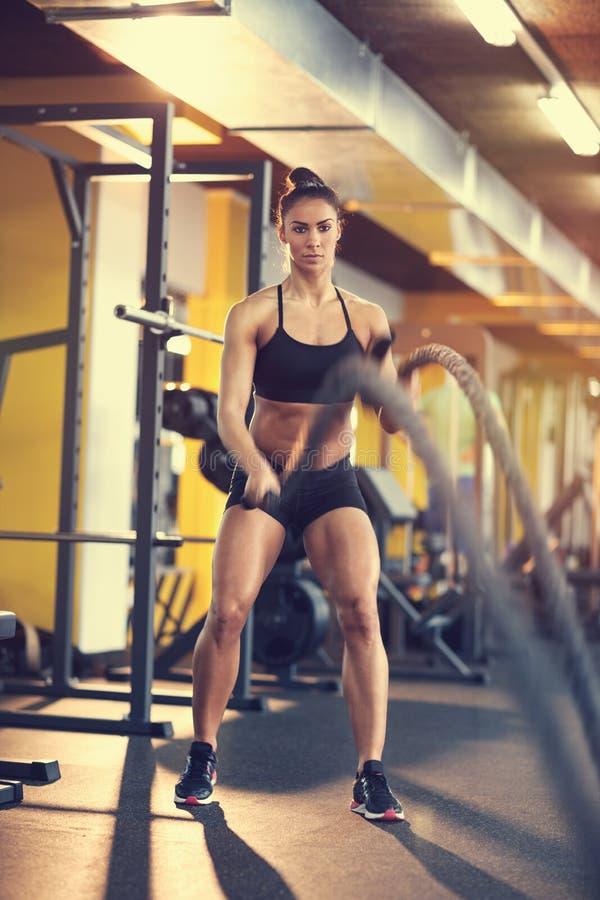 Sportvrouwoefening met kabel in gymnastiek royalty-vrije stock afbeelding