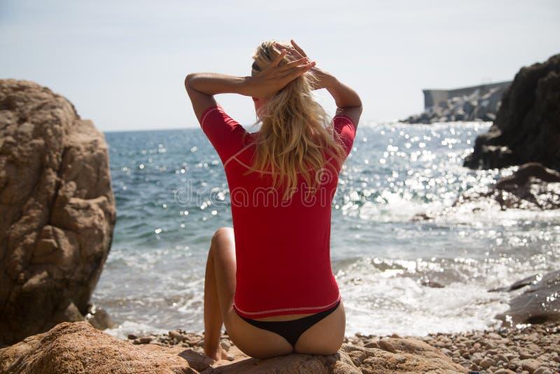 sportwear的性感的在多岩石的海滩的女孩和tanga 免版税库存照片