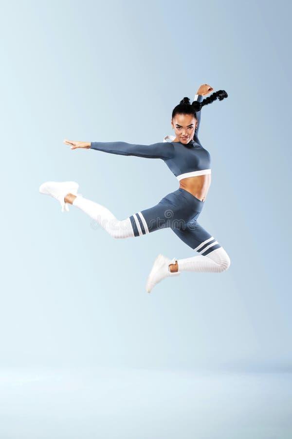 sportwear跳跃的可爱的激动的健身女孩舞蹈家喜悦被隔绝在灰色背景 库存照片