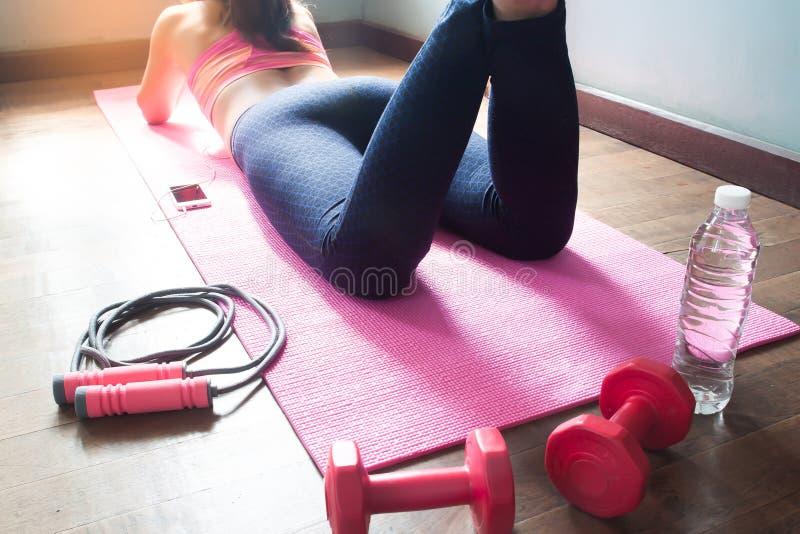 Sportwear d'uso della giovane donna adatta che si rilassa dopo l'allenamento a casa immagine stock libera da diritti