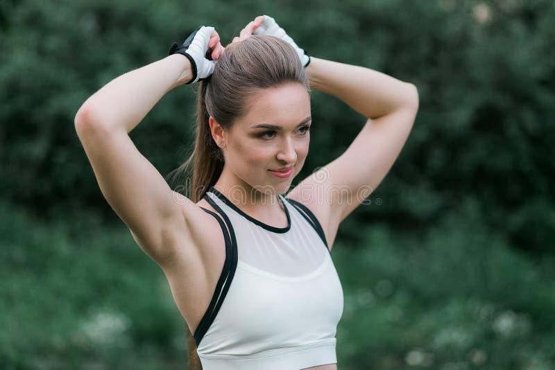 Sportwear que lleva de la mujer joven que toca su peinado al aire libre Retrato del primer foto de archivo libre de regalías