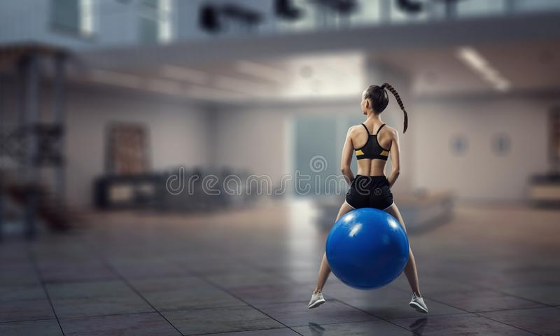 Sporty женщина на шарике фитнеса Мультимедиа стоковое фото rf