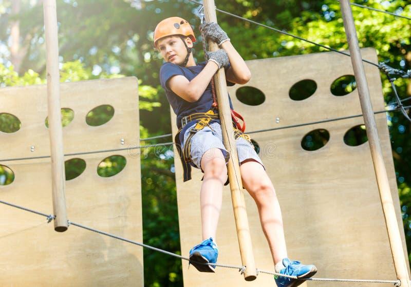Sporty, молодой, милый мальчик в белой футболке тратит его время в парке веревочки приключения в шлеме и безопасном оборудовании  стоковые фотографии rf