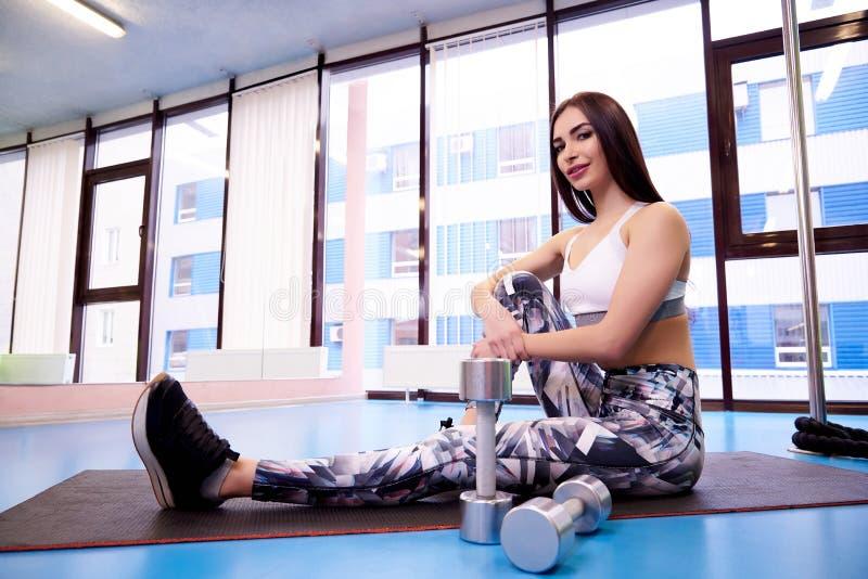 Sporty девушка сидя на циновке в спортзале с гантелями стоковое фото rf