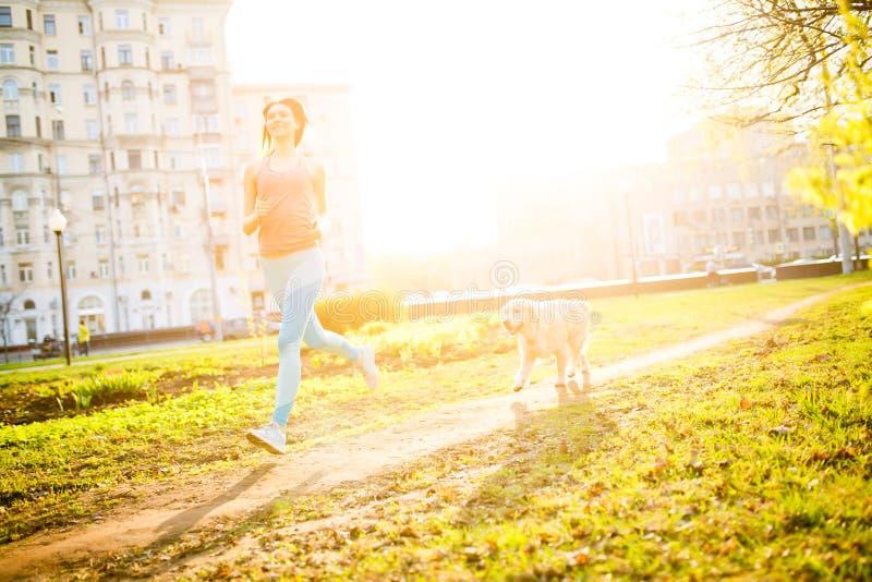Sporty девушка бежать с собакой стоковые фотографии rf