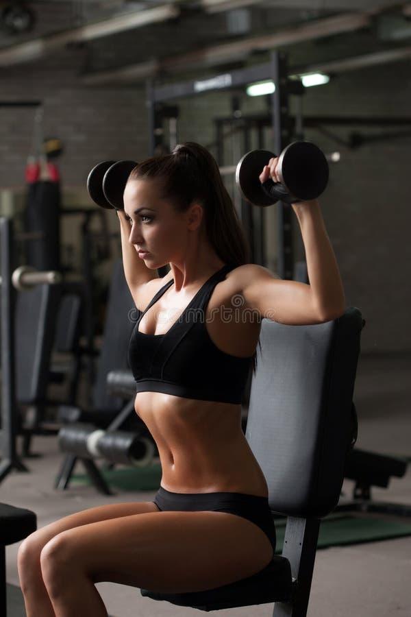 Sporty девушка работая с гантелями в спортзале стоковая фотография rf