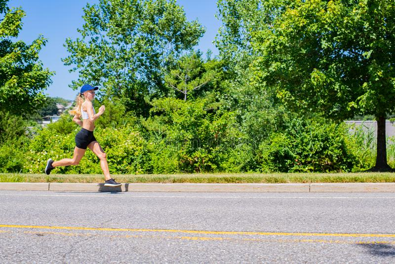 Sporty женщина в ходе следа sportswear на дороге Девушка спортсмена jogging в парке стоковые изображения