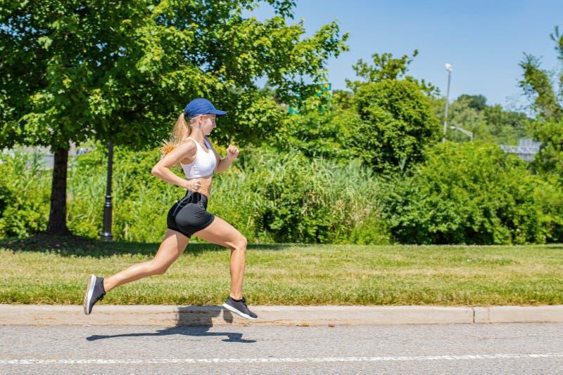 Sporty женщина в ходе следа sportswear на дороге Девушка спортсмена jogging в парке стоковое изображение rf