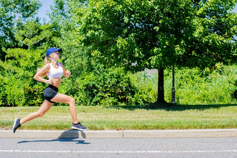 Sporty женщина в ходе следа sportswear на дороге Девушка спортсмена jogging в парке стоковое фото rf