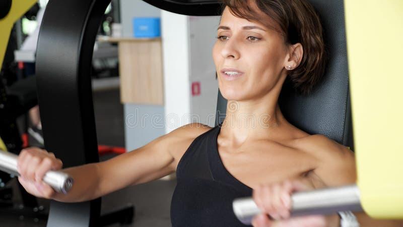 Sporty женщина делает тренировки для мышц оружий на тренируя машине стоковое изображение rf