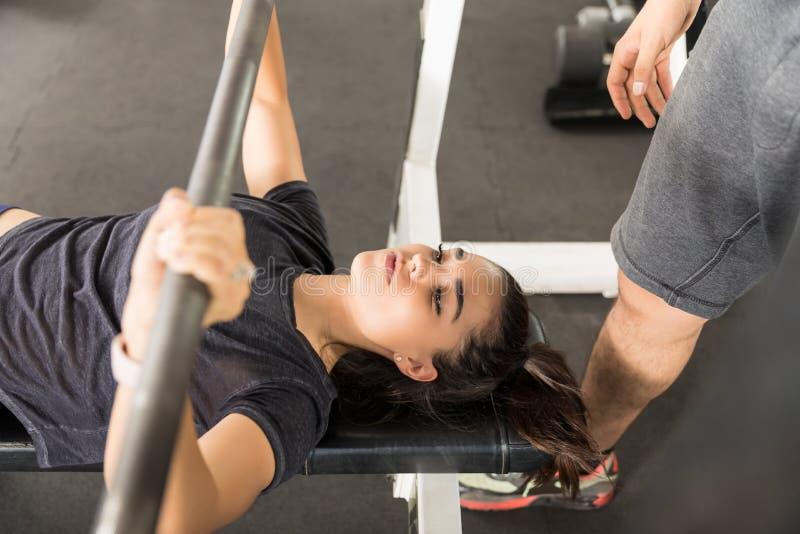 Sporty женщина делая жим лёжа в спортзале стоковые фото