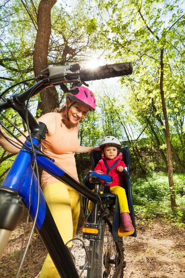 Sporty женщина ехать ее дочь в месте велосипеда стоковые фотографии rf