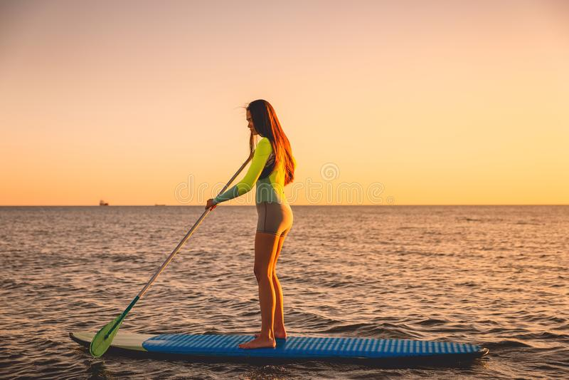 Sporty женщина на стоит вверх доска затвора с красочными цветами захода солнца стоковое изображение