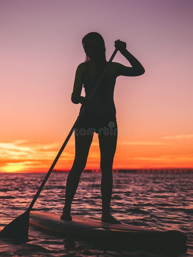 Sporty женщина на стоит вверх доска затвора на тихом море с яркими заходом солнца или восходом солнца стоковые изображения rf