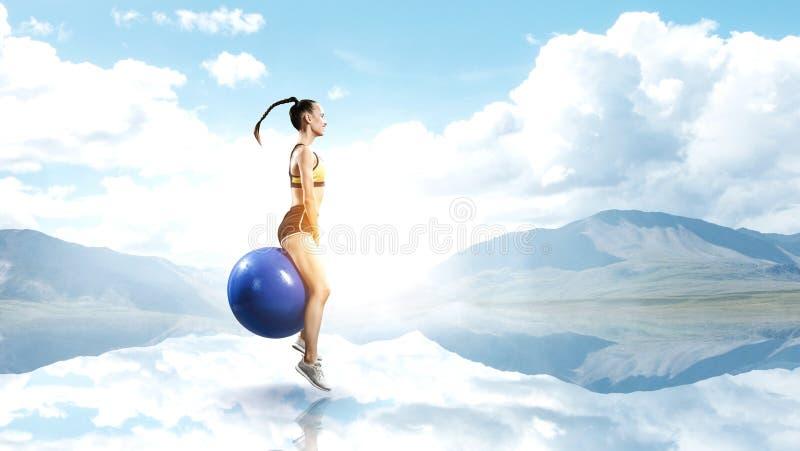 Sporty женщина на шарике фитнеса r стоковое фото