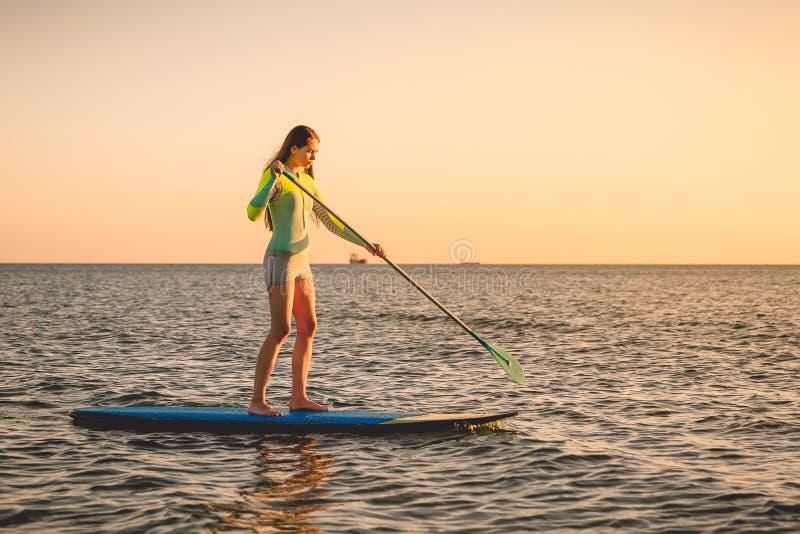Sporty женщина плавая на доску затвора стойки вверх с красочными цветами захода солнца стоковые изображения