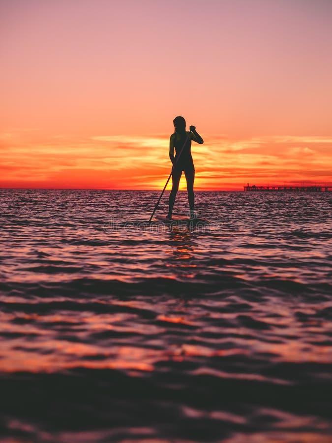 Sporty женщина стоит вверх восхождение на борт затвора на плоском теплом тихом море с ярким заходом солнца стоковые фотографии rf