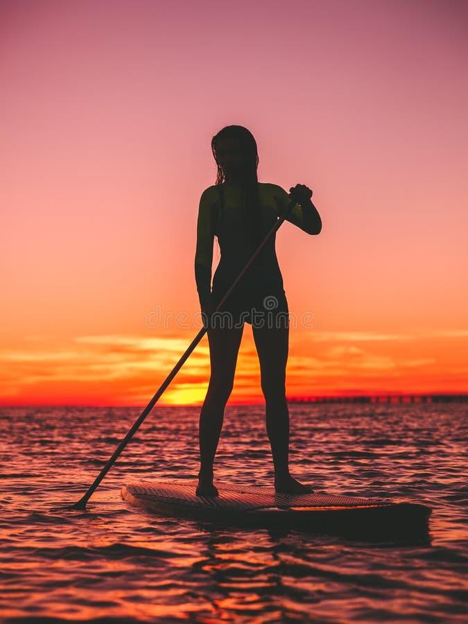 Sporty женщина стоит вверх восхождение на борт затвора на сумраке на плоском теплом тихом море с красивым заходом солнца стоковая фотография