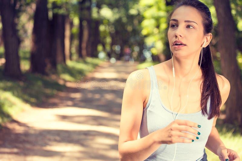 Sporty женщина jogging в парке в свете восхода солнца стоковая фотография rf
