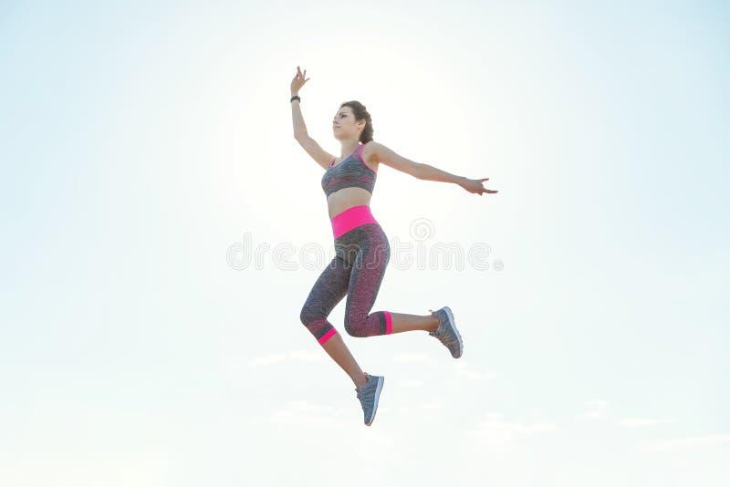 Sporty маленькая девочка в утре на пристани в скачке, практикуя йоге Женщина делает гимнастику outdoors концепция здоровья и йоги стоковое фото rf