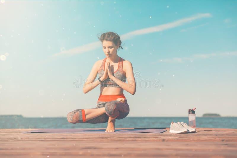Sporty маленькая девочка в утре на пристани на seashore, практикуя йоге Женщина делает гимнастику outdoors Здоровье и йога стоковая фотография