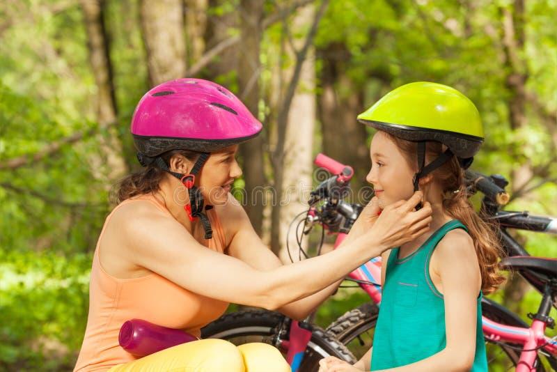 Sporty мать помогая ее дочери сжимать шлем стоковая фотография rf