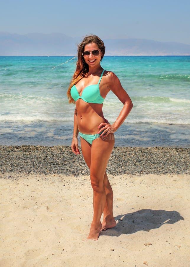 Sporty молодая женщина в свете - голубом бикини, нося солнечных очках, солнце стоковое фото