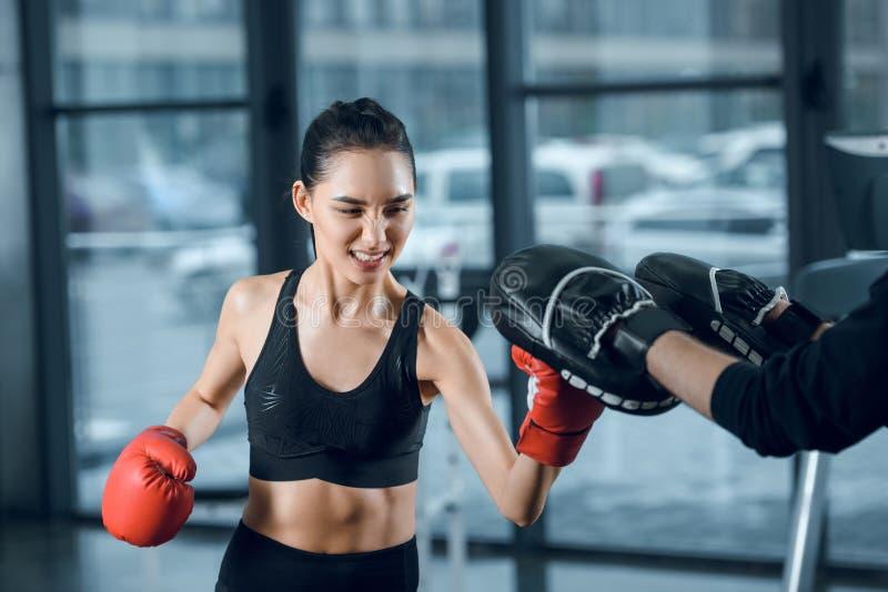 sporty молодой женский боксер работая с тренером стоковое изображение rf