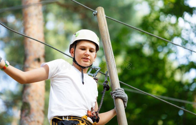 Sporty, молодой, милый мальчик в белой футболке тратит его время в парке веревочки приключения в шлеме и безопасном оборудовании  стоковые фото