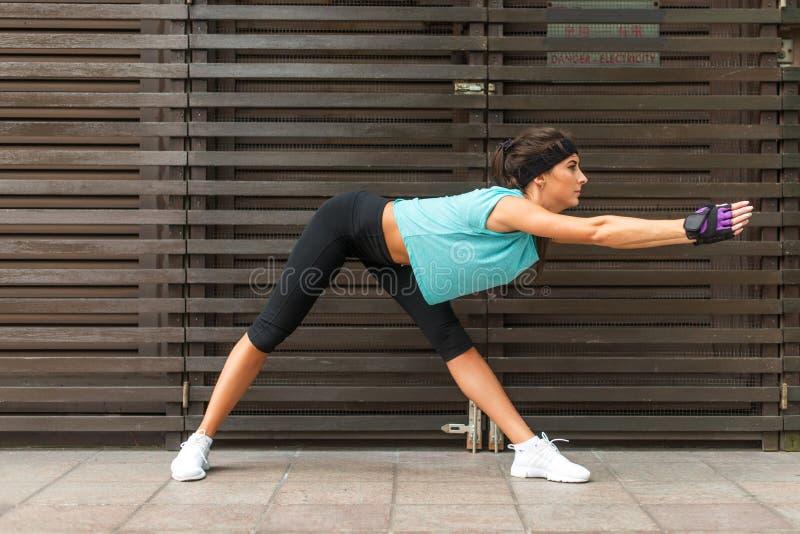 Sporty молодая женщина делая широк-шагающую переднюю тренировку загиба держа ее оружия прямой на улице города стоковое фото rf