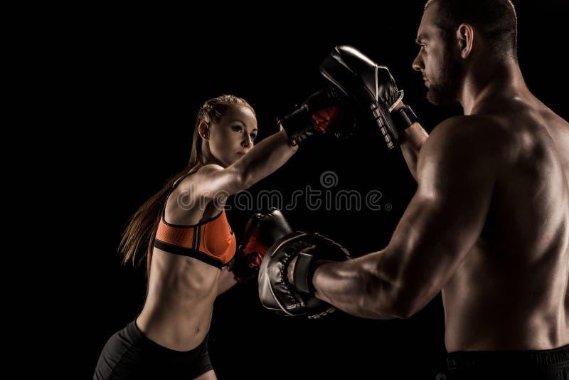 Sporty мышечные молодой человек и женщина кладя в коробку совместно стоковые изображения rf