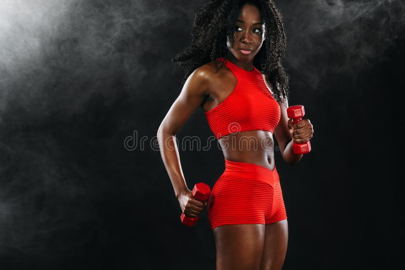Sporty подходящая черная женщина в красном sportswear, спортсмен кожи с гантелями делает фитнес работая на темной предпосылке стоковое изображение rf